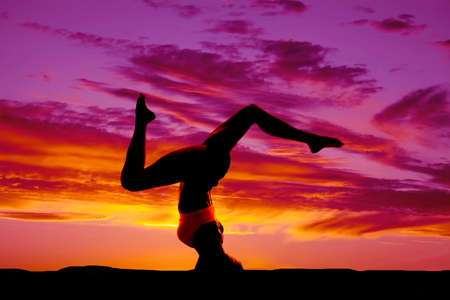 headstand: a silhouette of a woman doing a headstand in the outdoors. Stock Photo