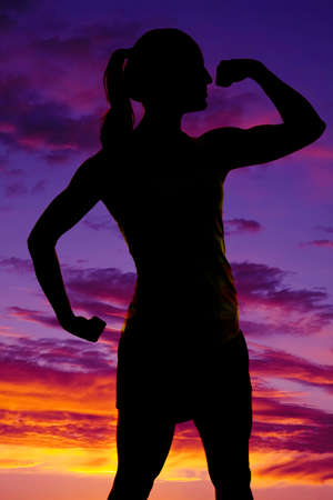 tight fit: A silhouette of a woman flexing her arms in the outdoors.
