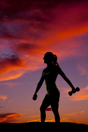a silhouette of a woman working out with weights in the outdoors.