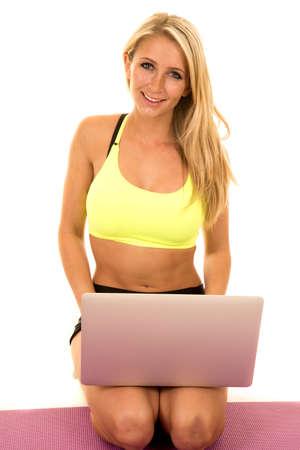 mujer rodillas: una mujer de rodillas con un ordenador portátil en su regazo, en busca de una sesión de ejercicios en el equipo. Foto de archivo