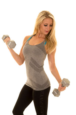 tight fit: a woman in her fitness clothing working out with weights.