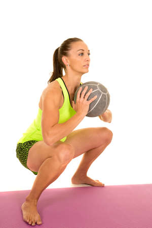 weighted: A woman doing  a squat with a weighted ball with serious expression.