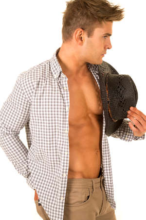 undone: A cowboy with his shirt undone showing off his fit chest holding on to his western hat. Stock Photo