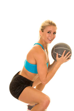 weighted: a woman doing a side squat with a weighted ball.