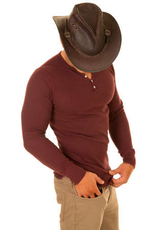 A cowboy looking down in his fit tight shirt. Banco de Imagens