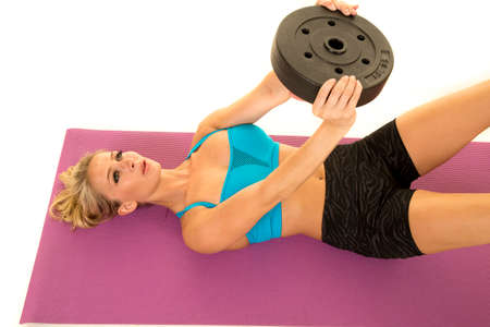 tight fit: a woman doing some ab crunches with a weight.