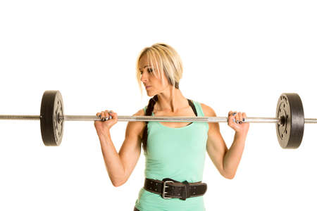 weighted: A woman holding on to a weighted bar looking to the side.