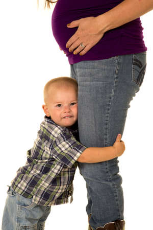 hugging legs: A pregnant mom with her little boy hugging her legs. Stock Photo