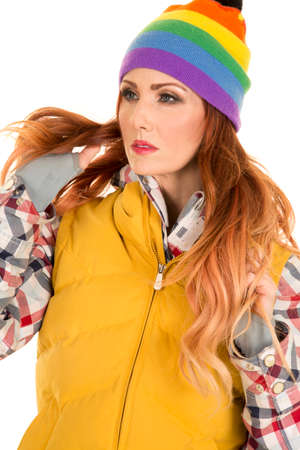 beanie: A woman in her winter coat and colorful beanie, looking away.