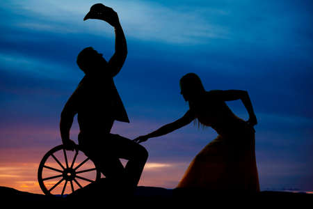 bending down: A silhouette of a woman bending down touching the leg of her cowboy. Stock Photo