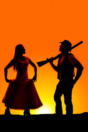 cowboy silhouette: A silhouette of a cowboy with a gun on his shoulder and his lady coming towards him. Stock Photo