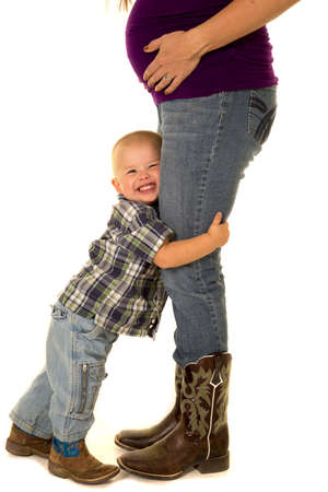 hugging legs: A pregnant woman with her little boy hugging her legs. Stock Photo