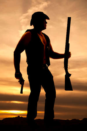 rancher: A silhouette of a cowboy, with his pistol and shotgun in his hand ready for a fight.