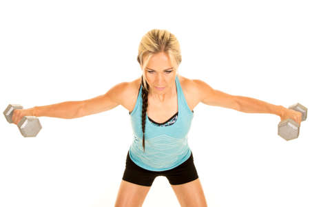 raises: a woman working on her shoulders doing lateral raises with weights.