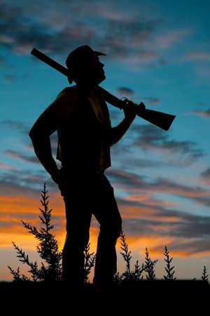 vaquero: una silueta de un vaquero de pie en las malas hierbas con una escopeta en el hombro. Foto de archivo