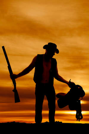 one armed: A silhouette of a cowboy holding on to his shotgun and saddle. Stock Photo