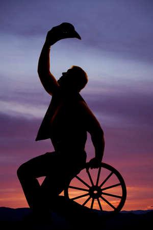 carreta madera: Una silueta de un vaquero que se sienta en una rueda de carro de madera con su sombrero hasta fuera de la cabeza. Foto de archivo