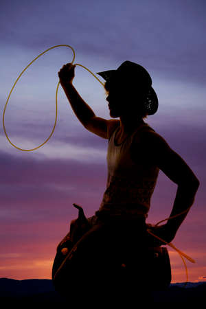 A silhouette of a cowboy with his rope ready to fly.