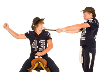 A teen cowboy in his football jersey swinging his ax at another player sitting on a saddle. Standard-Bild