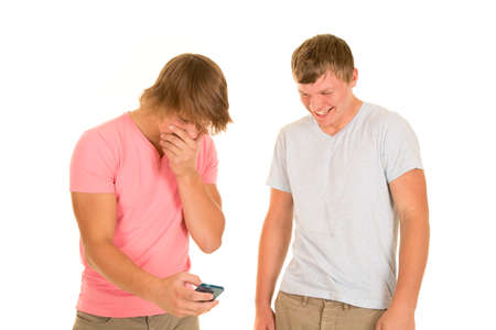 laughing: Two teenage boys laughing at a text one of them just received on his phone Stock Photo