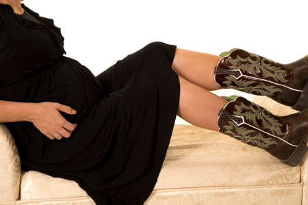 laying on back: A close up of a pregnant woman laying back on her couch showing off her western boots. Stock Photo