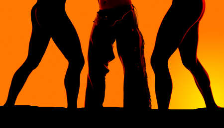 poised: A close up of womens legs with a cowboy in his chaps. Stock Photo