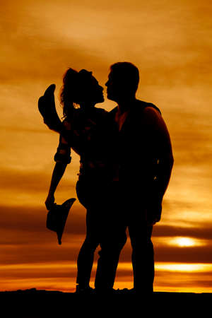 poised: A silhouette of a cowboy holding his cowgirl close in the outdoors.