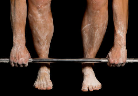 A close up of a woman's legs and arms covered in white powder dead lifting. Stock Photo