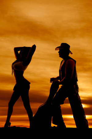 love silhouette: A silhouette of a man with a guitar and cowboy hat behind a woman. Stock Photo