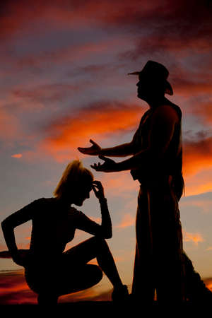 woman kneeling: A silhouette of a woman kneeling down, with her cowboy reaching out. Stock Photo