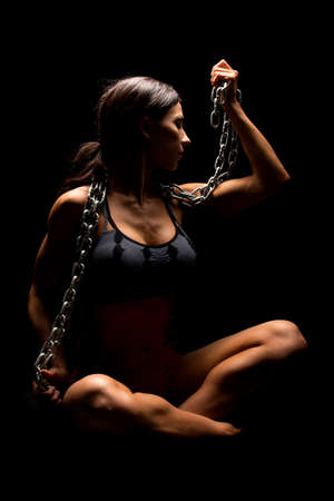 A woman in a black and gray sports bra with a chain around her neck. Stock Photo