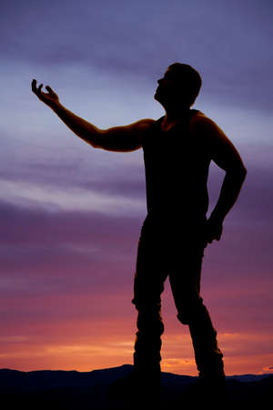 A silhouette of a man reaching out his hand towards the sky. photo