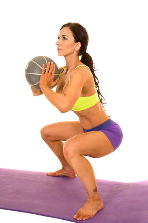 a woman in her fitness clothing, doing a squat with a medicine ball.
