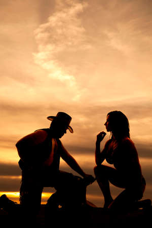 woman kneeling: A silhouette of a woman kneeling with her cowboy. Stock Photo