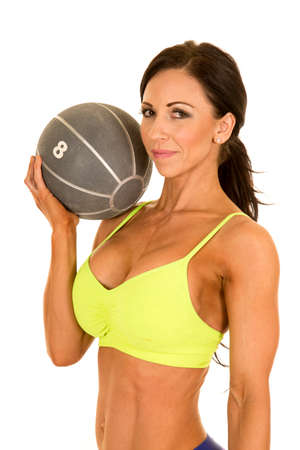 female sexy chains: a woman in her fitness clothing holding on to her medicine ball close to her.