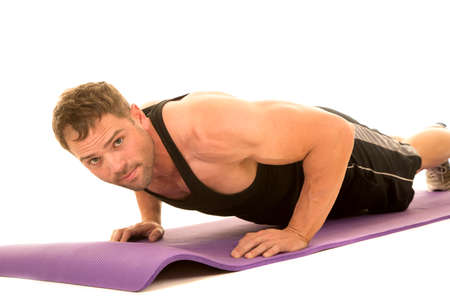 flexed: a man doing a push up on his fitness mat, working out his body.