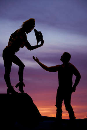 reaching up: a man reaching up to his cowgirl offering her help down off the cliff.