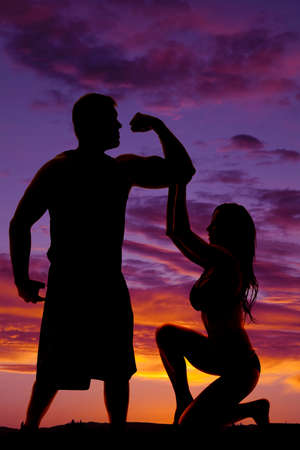 mujer rodillas: Una silueta de una mujer de rodillas hacia abajo con la mano en el brazo de su hombre, él es flexionar sus músculos. Foto de archivo