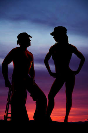 a silhouette of a cowboy sitting and his woman standing close to him. photo