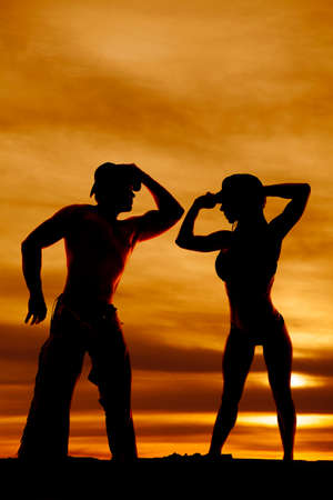 A silhouette of a cowboy leaning in to his woman. photo