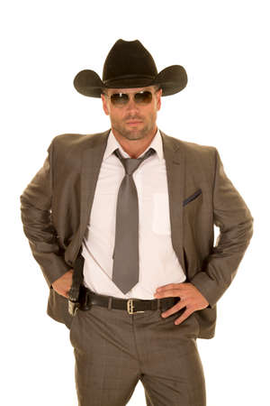A cowboy in his suit holding on to his pistol on his hip. Archivio Fotografico