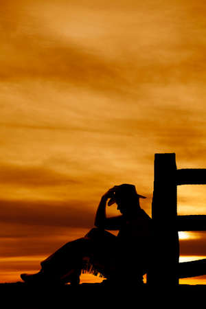 a silhouette of a cowboy sitting by a fence post touching his hat. photo