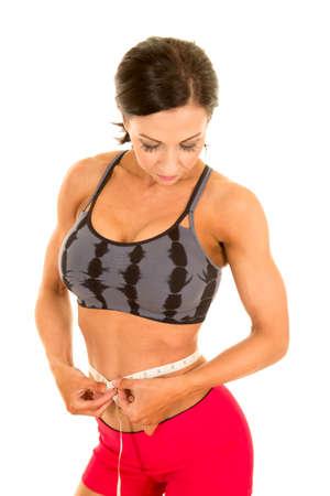 waist down: a woman looking down measuring her waist. Stock Photo