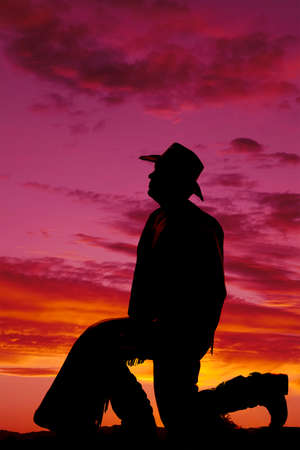 A silhouette of a cowboy kneeling and looking up to the sky. photo