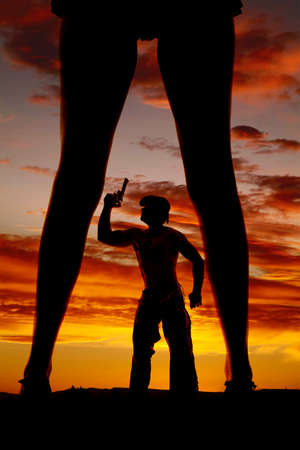 A silhouette of a cowboy in the middle of a woman's legs. photo