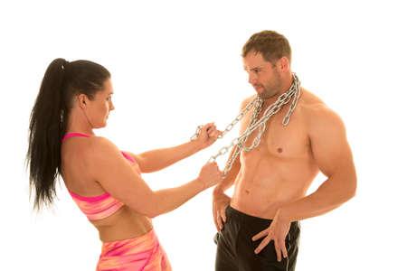 flexed: a woman in her fitness clothing pulling on her mans chain around his shirt.
