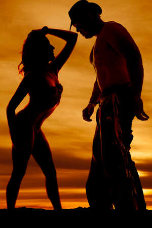 A silhouette of a woman posing her body in front of her cowboy. photo