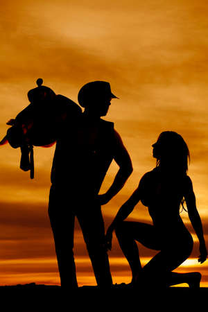 woman kneeling: a silhouette of a woman kneeling down in front of her cowboy while he is holding onto a saddle.