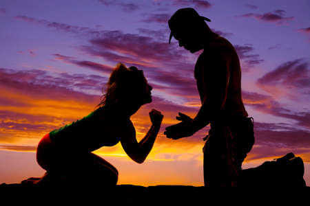 a silhouette of a woman begging her cowboy to stay.