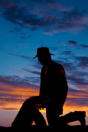 a silhouette of a cowboy on his knees praying. photo